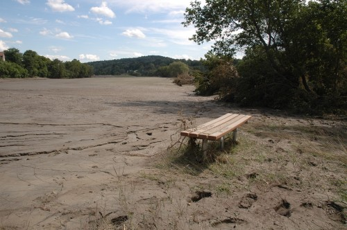 A lone park bench sits in a sea of silt at The Quechee Green recreation area. The verdant riverside park is now a brown wasteland. VTD/Andrew Nemethy