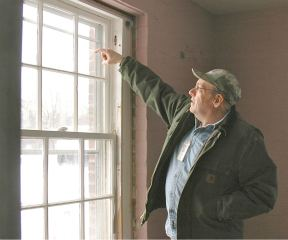 Waterbury State Complex supervisor Kevin Rogers points to the waterline in the Vermont State Hospital admissions office.
