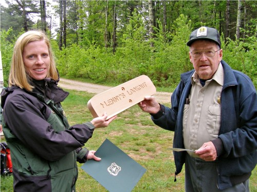 Holly Knox, Trails and Recreation Coordinator for the Green Mountain National Forest, shows off the woodcrafted sign that will officially name a trail and scenic lookout for campground host Lennie Waltrip at the Silver Lake National Forest Campground in Leicester. Photo by M. Dickey Drysdale