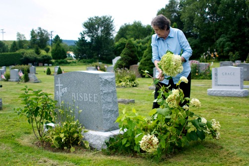 Mary Alice Brisbee, information director of the  Funeral Consumers Alliance of Vermont, wants to make it easier for Vermonters to be buried burial without caskets and gravestones, if they so wish. Here, she tends flowers at her mother's grave in Holy Cross Cemetery in Duxbury, where she doesn't want be buried. Photo by Viola Gad/VTDigger