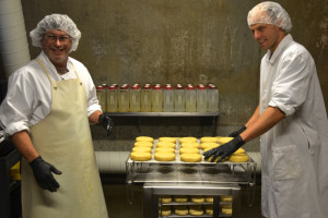 "Stuart Gaboriault, left, and Tim Gifford apply a cider ""wash"" to the rind of some Winnimere cheese in a ripening cellar at Jasper Hill Farm. The 14 cheeses in the cellars  each have their own complex regimen and requirements for aging, which provides the flavor that can distinguish an award-winning cheese. Photo by Andrew Nemethy"