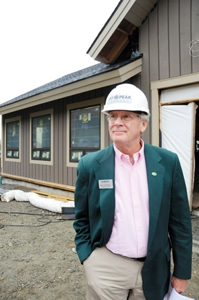 Bill Stenger stands before the future Stateside Hotel at Jay Peak. He predicts it will open to guests by December, after only starting construction in April. Photo by Hilary Niles/VTDigger