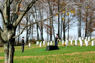 Honor Guard: Unwilling to allow even autumn's leaves to distract from the focus of an interment, Bob Durkee sweeps the bright green lawn clear where the honor guard awaits the burial. Photo by Nancy Graff