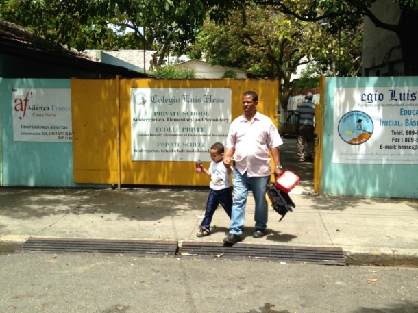A father escorts his son from his morning at school. In the Dominican Republic it is not at all uncommon to see males playing an active role in the raising of their kids.  Photo by Bob Stannard