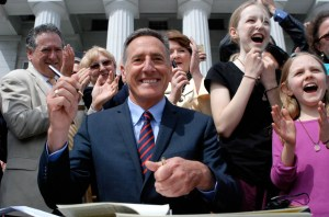Vermont Gov. Peter Shumlin on Thursday signed Vermont's first-in-the-nation GMO labeling bill into law on the Statehouse steps in Montpelier. Joining him was Brigid Armbrust, 11, of West Hartford (in black), who launched a letter-writing campaign in support of GMO labeling. Photo by John Herrick/VTDigger