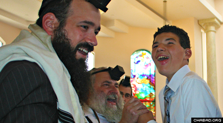 Parker Lynch celebrates his bar mitzvah at Chabad of Poway with Rabbi Mendy Rubenfeld, left and Rabbi Yisroel Goldstein, center.