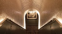 he barrel-vaulted stairwell, covered in platinum mosaic tiles, leading to the Sense spa.