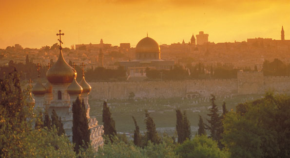 Jerusalem's old city walls and the Dome of the Rock as seen from the Mount of Olives observation point near the golden onion domes of the Russian Orthodox Church of Mary Magdalene.
