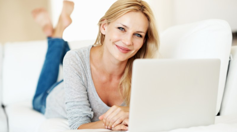 Portrait of smiling woman lying while working on laptop at home