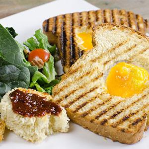 Dos huevos estrellados sobre un marco de pan con mantequilla, acompañado de chillo hecho en casa.