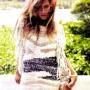 Gisele Bundchen con blusa tejida rusticamente, cabello desordenado y pantalones cortos de mezclilla deslavados.