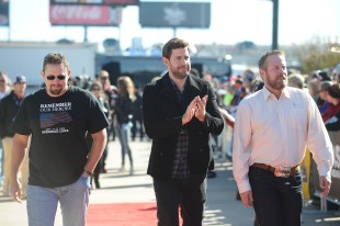 """FORT WORTH, TX - NOVEMBER 08: Actor John Krasinski (C) and U.S. security team members Mark """"Oz"""" Geist (R) and John """"Tig"""" Tiegen (L) arrive on the red carpet to the driver's meeting prior to the NASCAR Sprint Cup Series AAA Texas 500 at Texas Motor Speedway on November 8, 2015 in Fort Worth, Texas. (Photo by Rainier Ehrhardt/NASCAR via Getty Images)"""