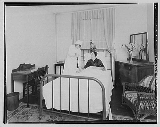 Nurse treating bed-ridden patient at sanatorium