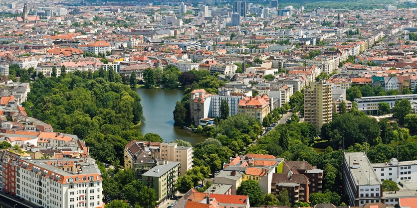 Aerial view across the tranquil oasis of the Lietzensee park and lake with its green parkland surrounded by the houses and streets, apartment blocks and office buildings of Charlottenburg, Berlin. ProPhoto RGB profile for maximum color fidelity and gamut.