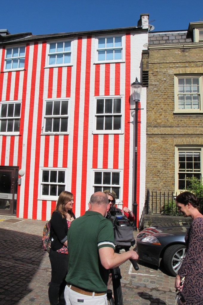 Stares and stipes: A Sky news crew interview locals outside the mews house