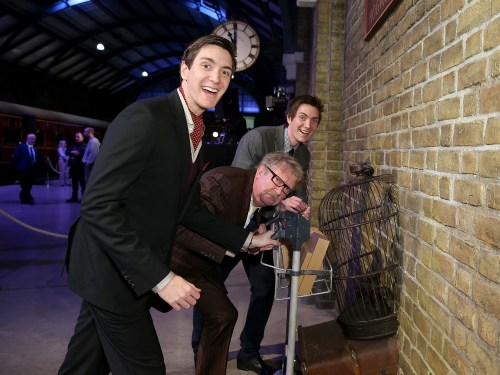 James Phelps, Mark Williams and Oliver Phelps pushes the luggage trolley on Platform 9 3/4 at Warner Bros. Studio Tour London