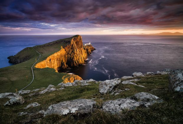 Mid-Summer dusk over Neist Point Lighthouse, Isle of Skye, London. The Isle of Lewis sits on the horizon. At this time of year, this region of Scotland receives around 17-18 hours of daylight per day.