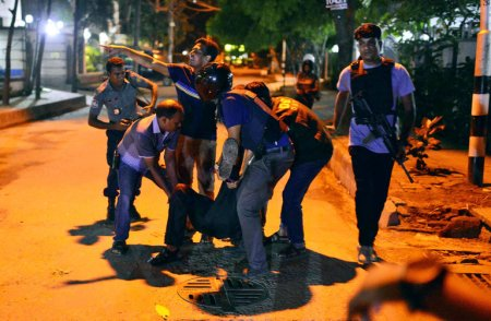 An injured person was helped after gunmen attacked a restaurant popular with foreigners in a diplomatic zone of Dhaka, the Bangladeshi capital, on Friday. Credit Associated Press