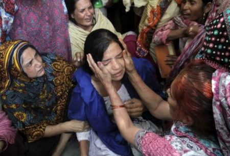 (PHOTO: REUTERS/MOHSIN RAZA) Family members comfort a woman mourns the death of a relative, who was killed in a blast outside a public park on Sunday, during funeral in Lahore, Pakistan, March 28, 2016.