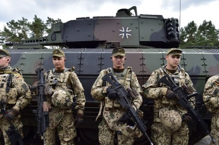 Soldiers of the 33rd Panzergrenadier bataillon stand ready for inspection in front of a Puma infantry fighting vehicle after taking part in a drill at the headquarters of the 33rd Panzergrenadier bataillon in Neustadt am Ruebenberge on June 29, 2016. / AFP PHOTO / JOHN MACDOUGALL