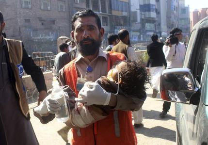 A Pakistani volunteer carries an injured child to a hospital in Peshawar, Pakistan, Tuesday, Feb. 21, 2017. Police say three suicide bombers have attacked a courthouse in northwestern Pakistan. Charsadda police chief says one of the bombers detonated his suicide vest at the court's main gate while police shot and killed the two other assailants. (AP Photo/Mohammad Sajjad)