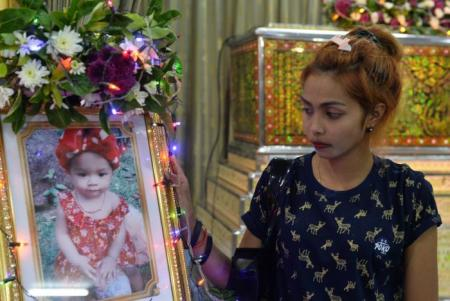 Jiranuch Trirat, mother of 11-month-old daughter who was killed by her father who broadcast the murder on Facebook, stands next to a picture of her daughter at a temple in Phuket, Thailand April 25, 2017. (REUTERS/Sooppharoek Teepapan)
