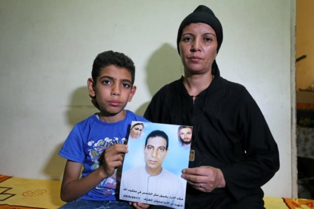 Hanaa Youssef and Mina Habib, the widow and son of a man who was killed in a militant attack against Coptic Christians last month, hold the victim's portrait in Minya, Egypt. (REUTERS/MOHAMED ABD EL GHANY)