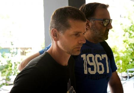 A Russian man (L) suspected of running a money laundering operation is escorted by a plain-clothes police officer to a court in Thessaloniki, Greece July 26, 2017. REUTERS/Alexandros Avramidis