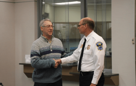 Earl Melchert, left, shakes hands with Alexandria, Minn., Police Chief Richard Wyffels on Friday as they both presented the reward to the kidnapped girl's family. (Alexandria Police Department)