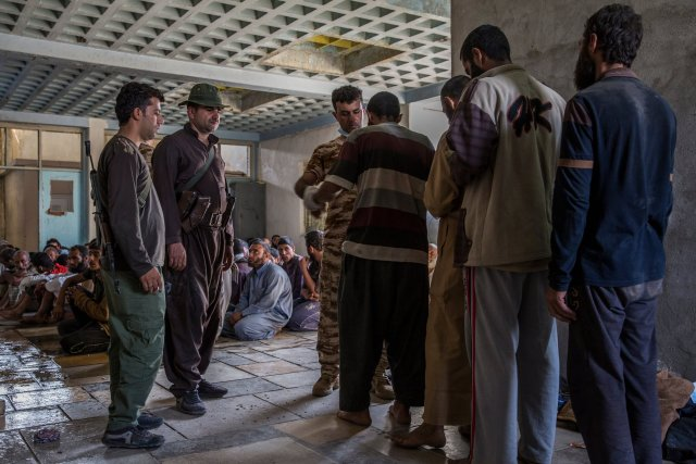 At the Kurdish screening center in Dibis, suspects are searched, their shoes taken, their pockets emptied and their belts discarded. Ivor Prickett for The New York Times