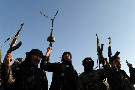 embers of the Free Syrian Army raise their weapons during a patrol in Idlib in northwestern Syria on February 18, 2012. A senior Chinese envoy called for all sides in Syria to stop the violence and for elections to go ahead peacefully after Damascus talks with President Bashar al-Assad, state media said. AFP PHOTO/BULENT KILIC (Photo credit should read BULENT KILIC/AFP/Getty Images)