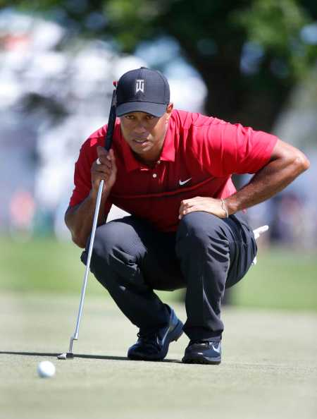 FILE - In this Feb. 25, 2018, file photo, Tiger Woods lines up a putt on the fourth hole during the final round of the Honda Classic golf tournament,in Palm Beach Gardens, Fla. Woods decided to add next week's Valspar Championship to his golf schedule leading up to the Masters. (AP Photo/Wilfredo Lee, File)