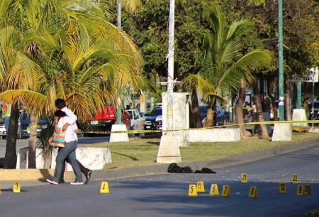 A couple walks past markers placed where bullet casings were found by investigators near the state prosecutors' office after gunmen opened fire on the building in Cancun, Mexico, Tuesday, Jan. 17, 2017. A witness said the gunmen tossed two explosive devices at a perimeter wall, and a reporter at the scene saw police remove a body from a guard post near the building after the attack.