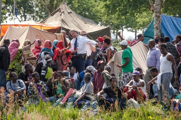 Nederland ter Apel 20120523 een politie officier probeert Somalische uitgeprocedeerde asielzoekers dringend maar nog vriendelijk het terrein te verlaten. Later zal ook de ME er aan te pas komen om de mensen te arresteren en af te voeren. foto Harry Cock/de Volkskrant