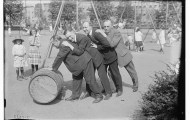just four men rolling a barrel in a park