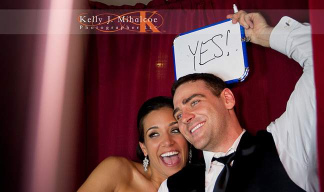 """Bride & Groom Holding a sign that says """"Yes!"""" over their heads in the Williamsburg Photo Booth"""