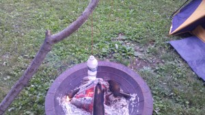 Plastic Bottle with Water Hanging Over Fire