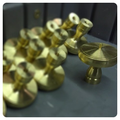 turned brass wayzata cabinet knobs starting to fill a bin