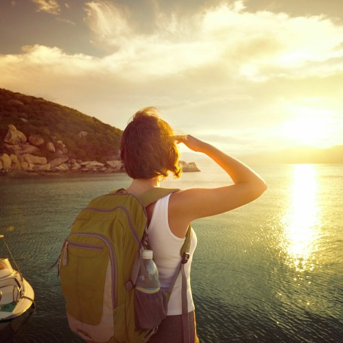 41822038 - young woman hiker standing on the coast and enjoying sunrise over the sea. traveling along asia active lifestyle concept