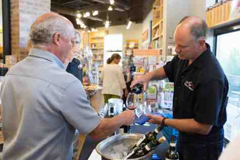 Jarrett Osborn of Riverwalk Wine & Spirits pouring a glass of Ca' del Baio Barbaresco Vallegrande for Dean Johnson.
