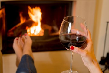 woman drinking wine in front of fire