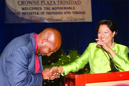 Photo: Sport Minister Anil Roberts (left) give his respects to his boss and Prime Minister Kamla Persad-Bissessar at a function. Careful PM; that bald head gets around.
