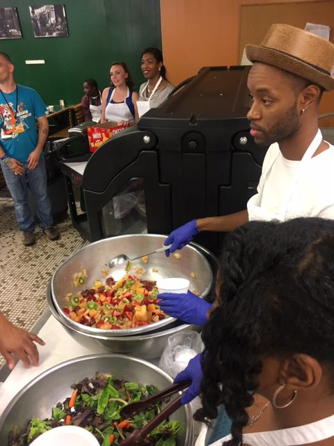 Myron Mollon serving salad during dinner in the Helping Up Mission Cafeteria