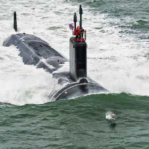 A Dolphin escorting the Navy's newest Submarine