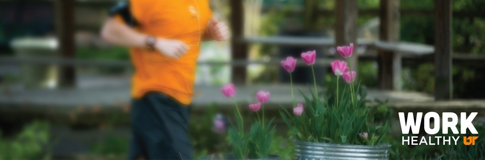 Runner in exercise clothes running behind tulips in the foreground