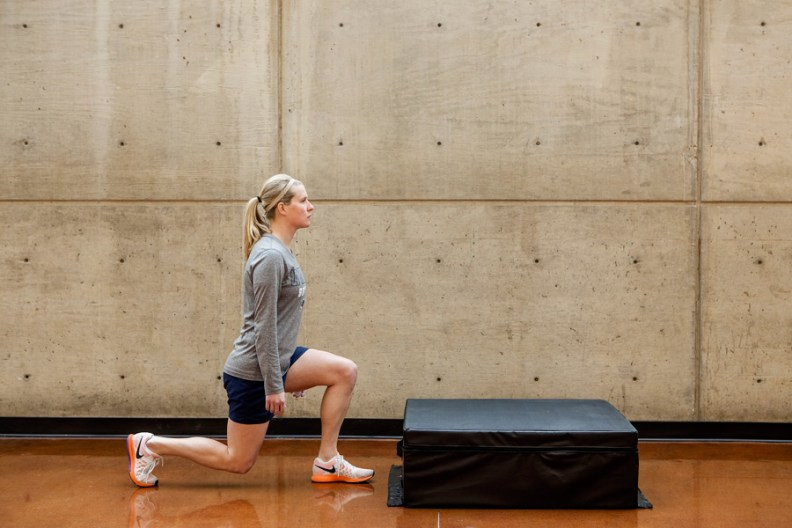 Leslie lunges in squat position with left foot forward and her right knee bend downward
