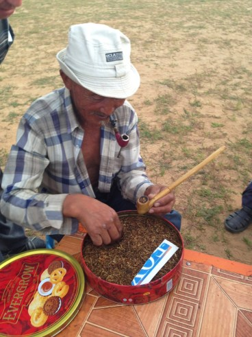 Our host preparing a pipe with tobacco.