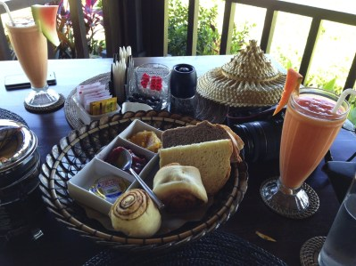 Fresh fruit plate, basket of bread and muffins with fresh jams, a fresh tropical fruit smoothie, Balinese coffee or tea and eggs with bacon.