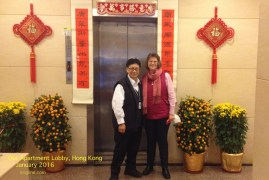 """Vivian poses with our very friendly morning """"Bao An"""" (security guard), in front of the New Year decorations in our apartment lobby."""