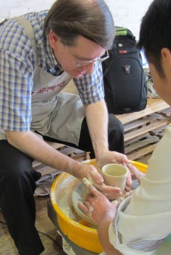 The potter's hands guide the hands of an amateur.